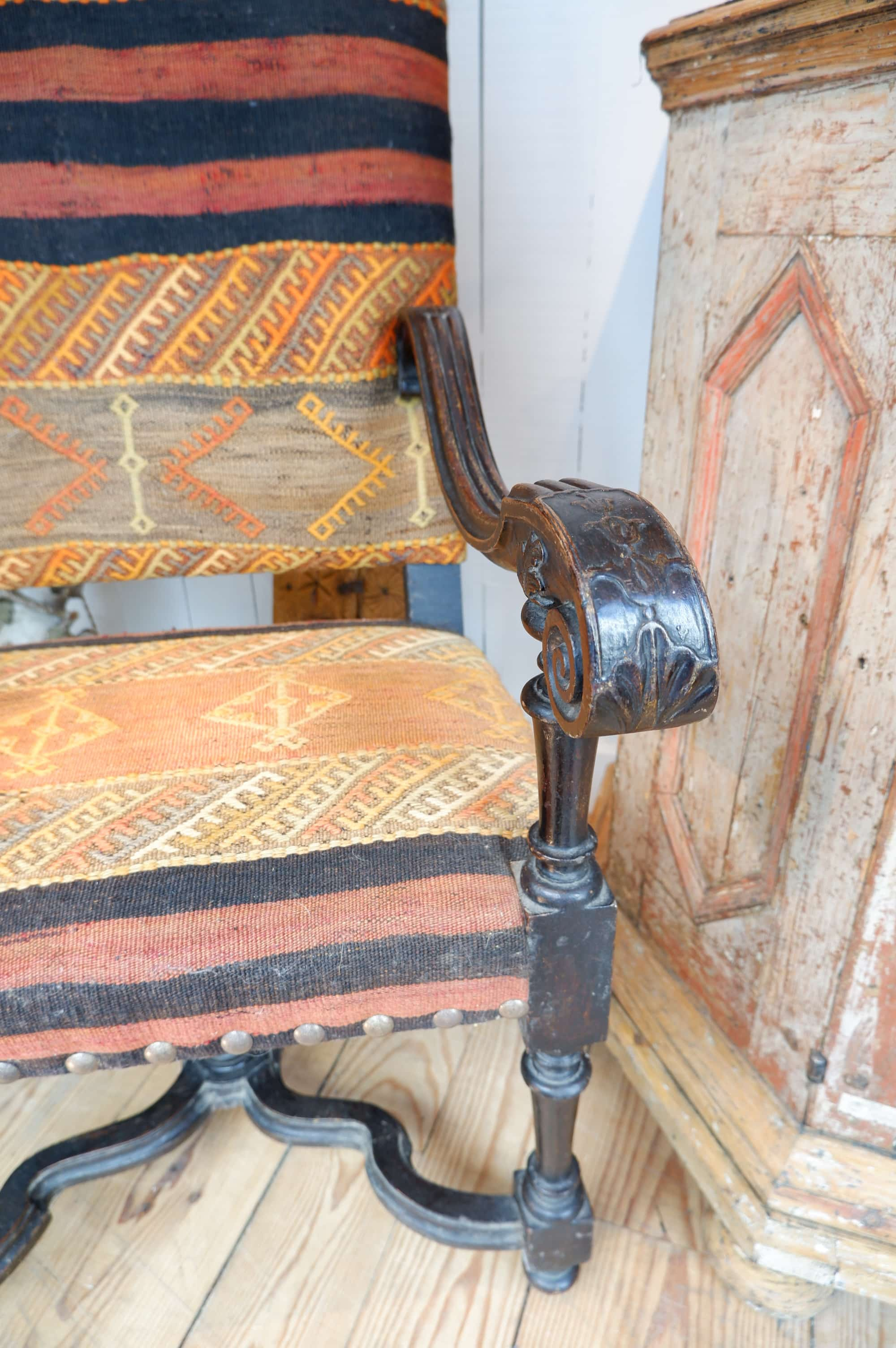 Louis XIII  tall armchair with dark patina covered with an antique Kilim Ca.1700