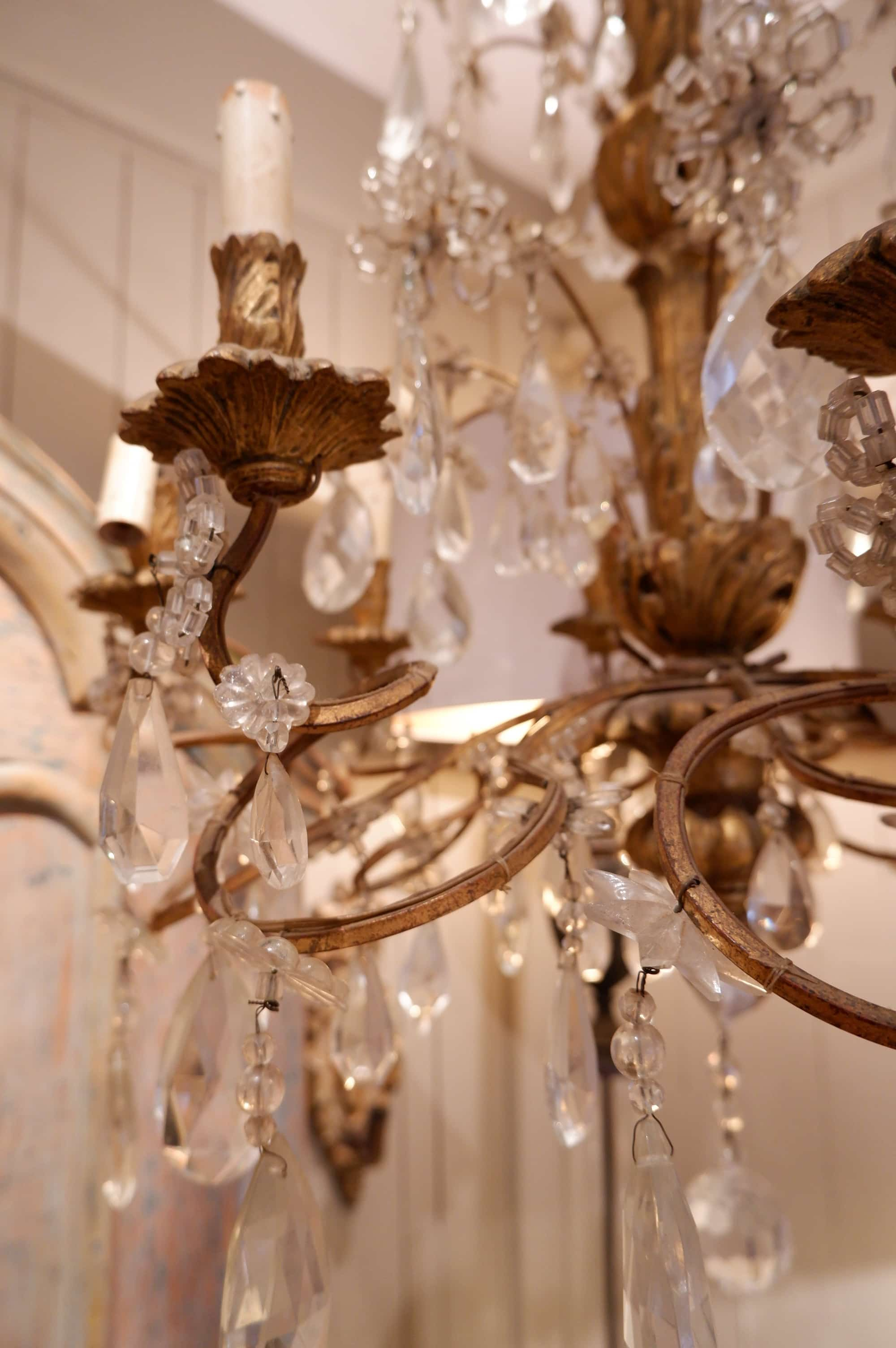 Lustre en métal patine bronze à volutes et pendants de verre fin XIXe