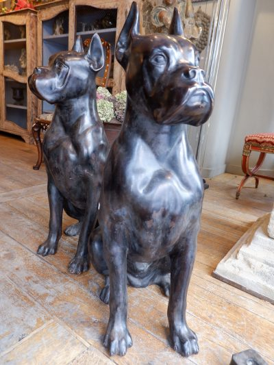 A pair of large sitting dogs in patinated bronze